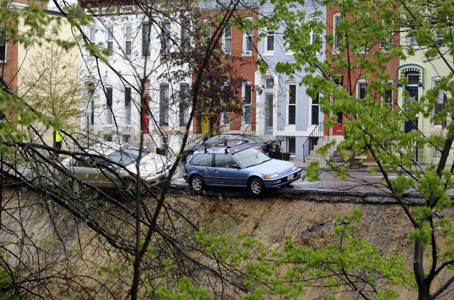 Cars sit on the edge of a sinkhole in the Charles Village neighborhood of Baltimore, Wednesday, April 30, 2014, as heavy rain moves through the region. Road closures have been reported due to floo ...