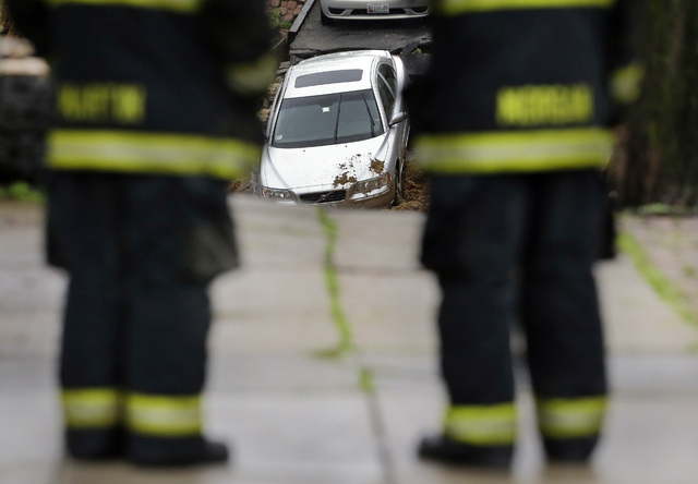 Firefighters look at a car sitting on the edge of a sinkhole in the Charles Village neighborhood of Baltimore, Wednesday, April 30, 2014, as heavy rain moves through the region. Road closures have ...
