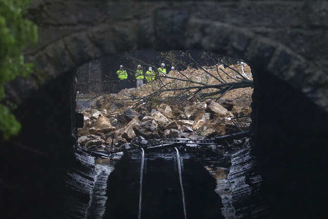 Emergency officials are seen through a CSX railroad tunnel near debris that fell onto tracks in the Charles Village neighborhood of Baltimore, Wednesday, April 30, 2014, as heavy rain moves throug ...
