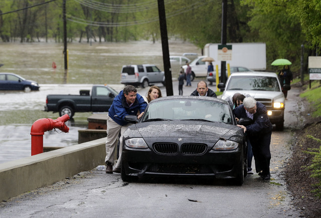 Employees from Learn It Systems help push coworker Russell Lum's car to higher ground after it was flooded in a parking lot, back, in Baltimore, Wednesday, April 30, 2014. Road closures have been  ...