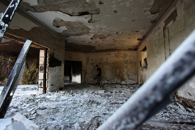 This Sept. 13, 2012 file photo shows a man walking in the rubble of the damaged U.S. consulate, after an attack that killed four Americans, including Ambassador Chris Stevens on the night of Tuesd ...