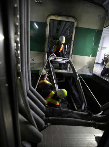 South Korea's subway workers try to repair the train at Sangwangshipri station after a collision  in Seoul, South Korea, Friday, May 2, 2014. The subway train hit another train stopped at the stat ...