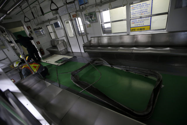 South Korea's subway workers try to repair a subway train after its collision at Sangwangshipri station in Seoul, South Korea, Friday, May 2, 2014. A subway train ran into another train at the sta ...