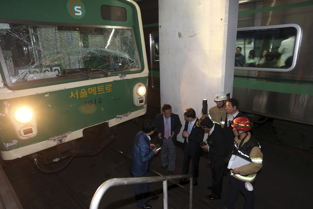 Investigators inspect the site where two subway trains collided at Sangwangshipri subway station in Seoul, South Korea, Friday, May. 2, 2014. A subway train plowed into another train stopped at th ...