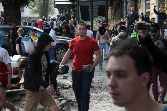 A Ukrainian government supporter carries stones during a clash with pro-Russians in the Black Sea port of Odessa, Ukraine, Friday, May 2, 2014. A clash broke out late Friday between pro-Russians a ...