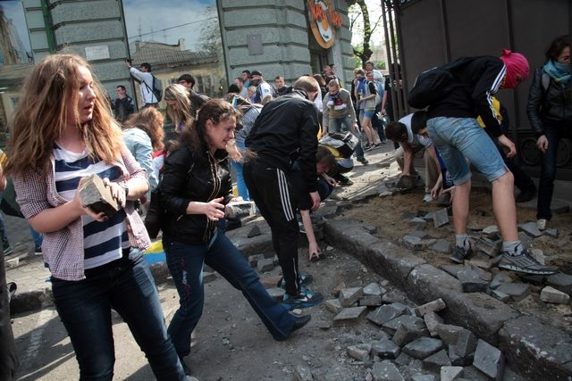Ukrainian government supporters dig for stones during a clash with pro-Russians in the Black Sea port of Odessa, Ukraine, Friday, May 2, 2014. A clash broke out late Friday between pro-Russians an ...