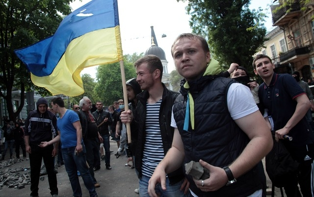 Ukrainian government supporters with a Ukrainian flag, prepare for a clash with pro-Russians in the Black Sea port of Odessa, Ukraine, Friday, May 2, 2014. A clash broke out late Friday between pr ...