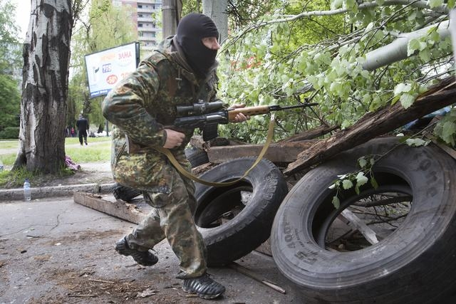 A Pro-Russian gunman runs behind barricades holding a weapon in Slovyansk, eastern Ukraine, Friday, May 2, 2014. Ukraine launched what appeared to be its first major assault against pro-Russian fo ...