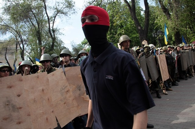 A Ukrainian government supporter walks past a line of self-defense activists during a clash with pro-Russians in the Black Sea port of Odessa, Ukraine, Friday, May 2, 2014. A clash broke out late  ...
