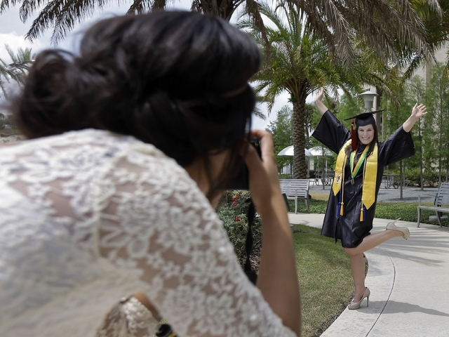 In this April 29, 2014 photo, University of South Florida graduating seniors Kyra Ciotti, 22, of Tampa, Fla., right, poses as Rita Sibaja, 24, of Winter Haven, Fla., takes photos of her in her cap ...