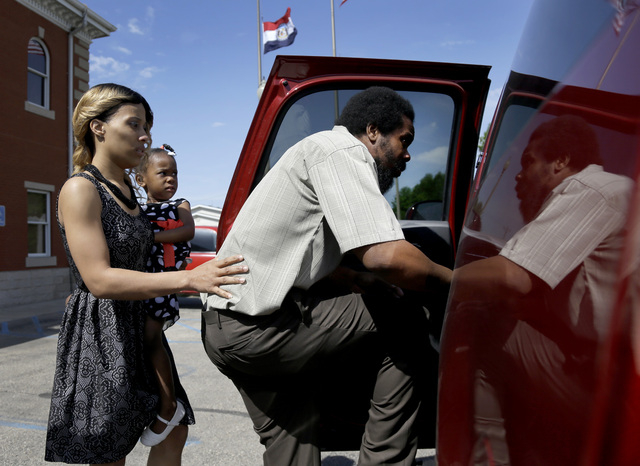 "Cornealious ""Mike"" Anderson, right, steps into a waiting car along with his wife, LaQonna Anderson, left, and daughter Nevaeh, 3, outside the Mississippi County Courthouse after being re ..."
