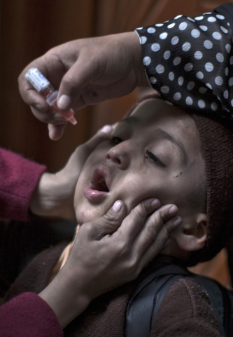 In this file photo dated Tuesday Jan. 21, 2014, a Pakistani health worker gives a child a polio vaccine at the door way of his home, while going house to house checking on children who need the va ...