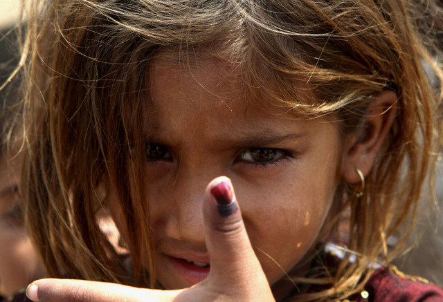 Pakistani girl Amina shows her thumb being marked after receiving polio vaccine in Lahore, Pakistan, Monday, May 5, 2014. For the first time ever, the World Health Organization on Monday declared  ...