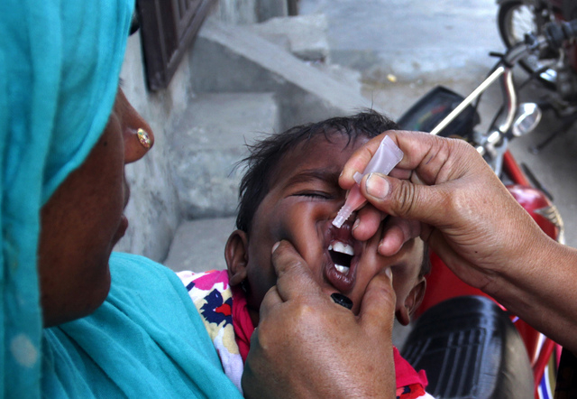 A Pakistani health worker gives a child a polio vaccine in Lahore, Pakistan, Monday, May 5, 2014. For the first time, the World Health Organization on Monday declared the spread of polio an intern ...
