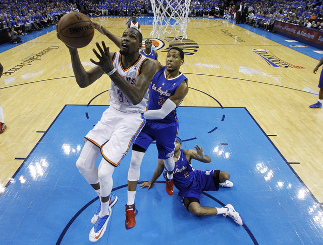 Oklahoma City Thunder forward Kevin Durant (35) goes up for a shot in front of Los Angeles Clippers forward Danny Granger (33) and forward Jared Dudley (9) in the second quarter of Game 1 of the W ...
