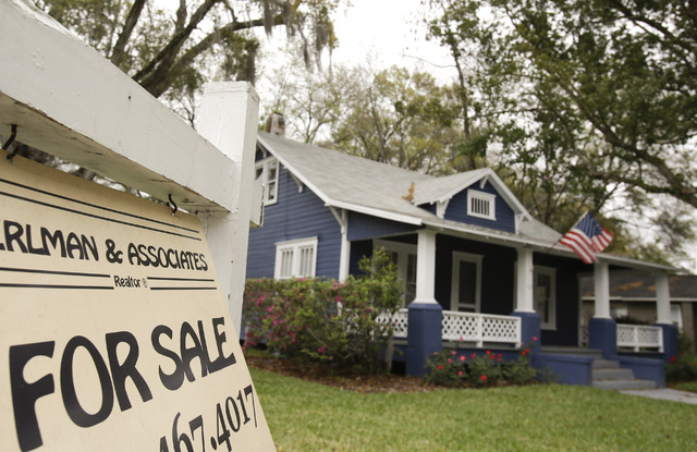 FILE- In this March 7, 2014, file photo, a realty sign hangs in front of a home for sale in Orlando, Fla. Real estate data provider CoreLogic reports on U.S. home prices in March on Tuesday, May 6 ...