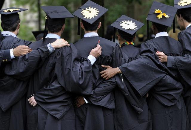 In this May 20, 2013 file photo, graduates pose for photographs during commencement at Yale University in New Haven, Conn. There's still plenty of pomp and circumstance, inspiring words from lofty ...