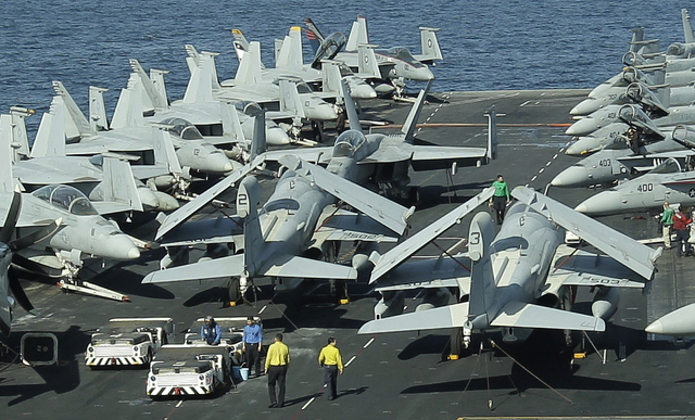 This file photo taken on Wednesday, Feb. 15, 2012, from the bridge of the Nimitz-class aircraft carrier USS Abraham Lincoln (CVN 72) shows U.S. aircraft  parked on the flight deck  in the Strait o ...