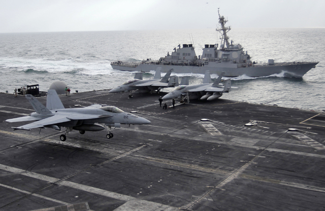 This file photo taken on Monday, Feb. 13, 2012 shows a U.S. F-18 fighter jet, left, land on the Nimitz-class aircraft carrier USS Abraham Lincoln (CVN 72) as a U.S. destroyer sells on alongside du ...