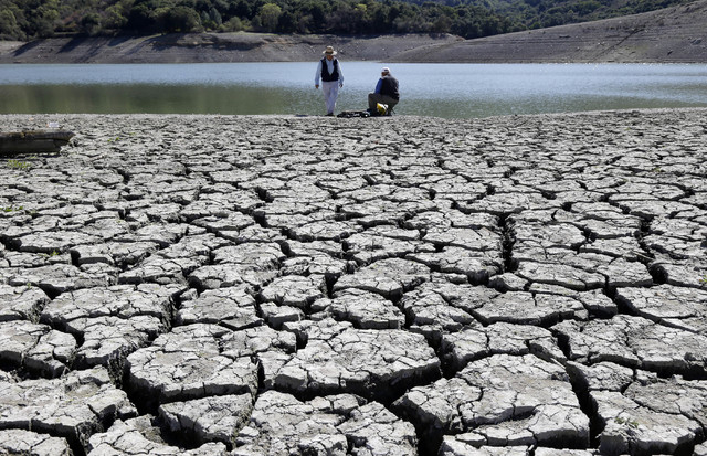 This March 13, 2014 photo shows cracks in the dry bed of the Stevens Creek Reservoir in Cupertino, Calif. The Obama administration is more certain than ever that global warming is changing America ...