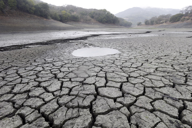 This Feb. 7, 2014, photo shows the cracked-dry bed of the Almaden Reservoir in San Jose, Calif.   Global warming is rapidly turning America the beautiful into America the stormy, sneezy and danger ...