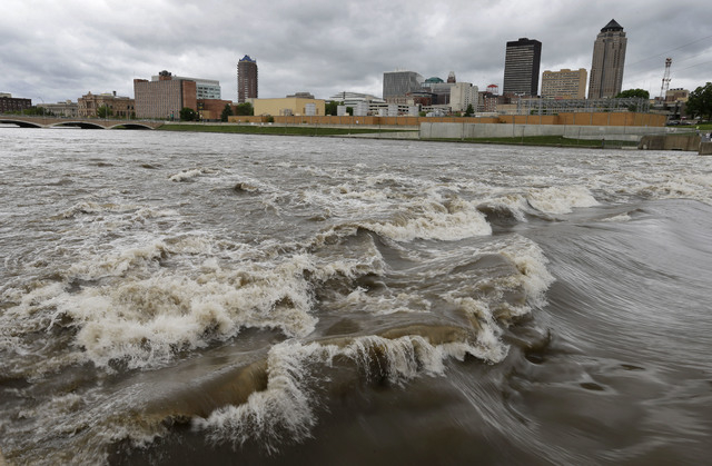 In this May 30, 2013, photo, water splashes over the Center Street Dam in the swollen Des Moines River in downtown Des Moines, Iowa.  Climate changes assorted harms are expected to become increasi ...