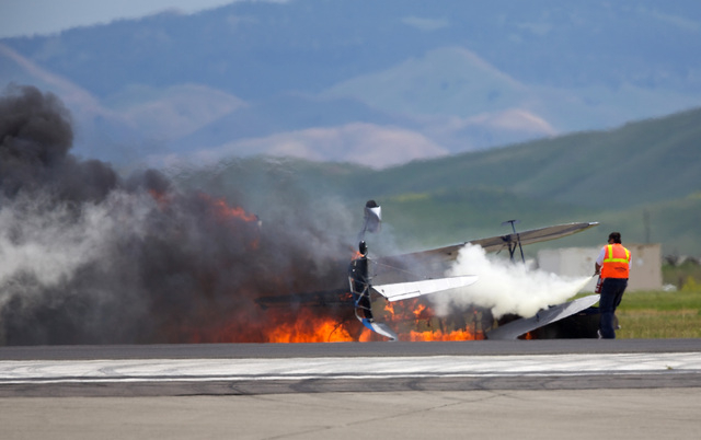 A worker fights a fire after a vintage biplane crashed upside-down on a runway at an air show at Travis Air Force Base in Fairfield, Calif., Sunday, May 4, 2014. The pilot, Edward Andreini, 77, of ...
