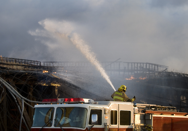 Firefighters try to contain a fire at a bridge construction site on Interstate 15 in Hesperia, Calif., on Tuesday, May 6, 2014.  The blaze, which burned through the night, reduced the bridge's woo ...