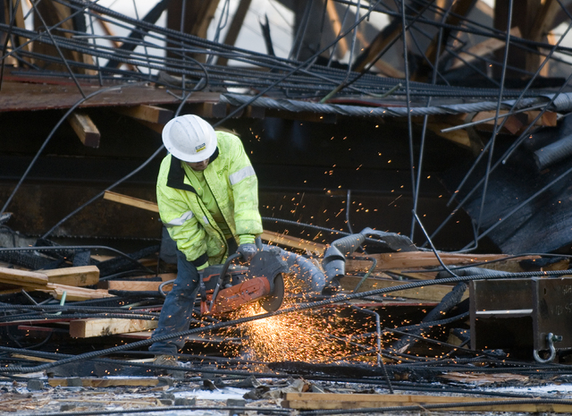 A contractor cuts steel re-bar as the remains of the Ranchero overcrossing bridge is torn down  in Hesperia, Calif., on Tuesday, May 6, 2014.  A fire on the bridge, which burned through the night, ...