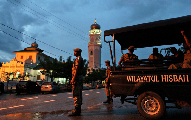 In this Dec. 31, 2013 file photo, Sharia police officers stand guard at a check point set up to prevent people from celebrating New Year's eve in Banda Aceh, Aceh Province, Indonesia. An Indonesia ...
