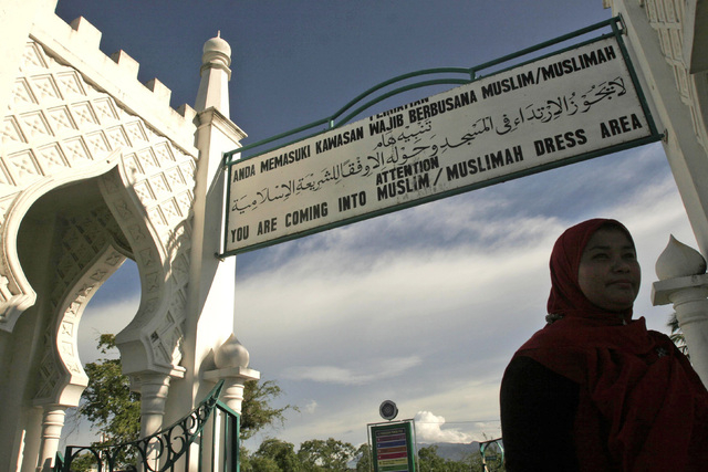 In this Sept. 13, 2009 file photo, a Muslim woman walks past beneath a sign advising people to wear Muslim attire at Baiturrahman Grand Mosque in Banda Aceh, Aceh province, Indonesia. An Indonesia ...