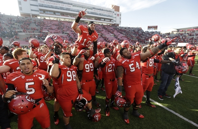 In this Nov. 30, 2013, file photo, Utah players celebrate at the end of their NCAA college football game against Colorado, in Salt Lake City. University of Utah President David Pershing says he ag ...