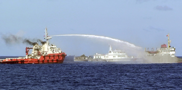 In this photo released by Vietnam Coast Guard, a Chinese ship, left, shoots water cannon at a Vietnamese vessel, right, while a Chinese Coast Guard ship, center, sails alongside in the South China ...
