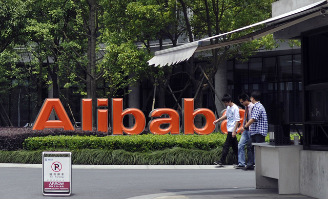 FILE - In this May 21, 2012 file photo, men walk past the corporate logo at the headquarters compound of Alibaba Group in Hangzhou in eastern China's Zhejiang province. Alibaba Group is aiming to  ...