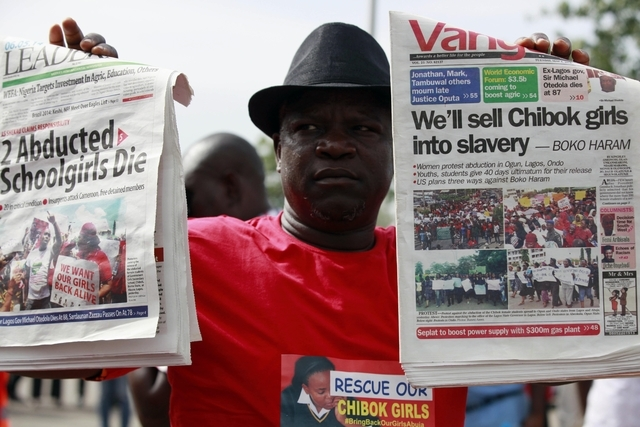 A man display copies of local newspapers during a demonstration calling on the government to rescue kidnapped school girls from Chibok government secondary school, outside the defense  headquarter ...