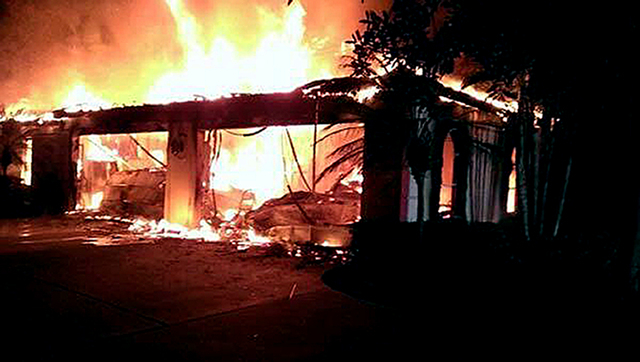 In this photo provided by the Hillsborough County Sheriff's Office, flames destroy a home in a gated community Wednesday May 7, 2014 in Tampa, Fla. Officials have confirmed that three bodies have  ...