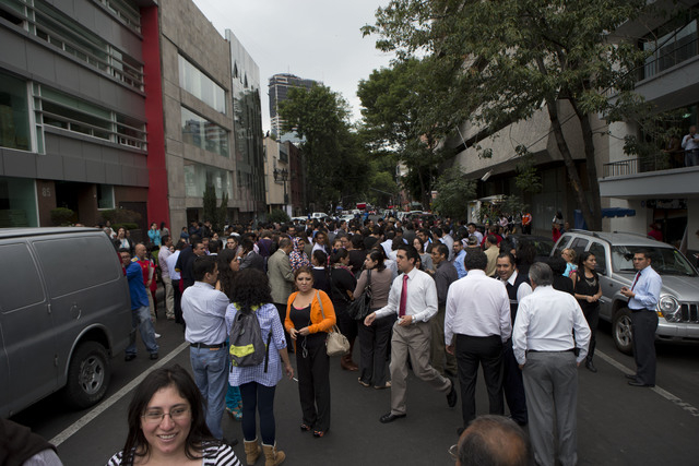 People gather in the street after an earthquake was felt in Mexico City, Thursday, May 8, 2014. A strong earthquake on the Pacific coast shook the capital, sending frightened office workers stream ...