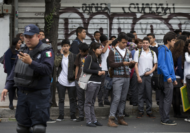 People stand on the side of the street as police try to reopen the street to cars after an earthquake shook Mexico City, Thursday, May 8, 2014. A strong earthquake in southern Guerrero state shook ...