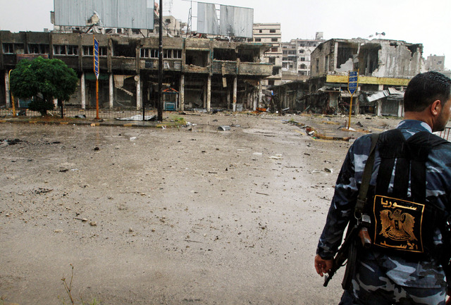 A Syrian government solider looks at damaged buildings in Homs, Syria, Thursday, May 8, 2014. Hundreds of exhausted Syrian rebels withdrew Wednesday from their last remaining strongholds in the he ...