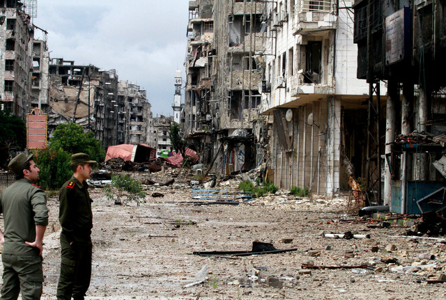 Syrian government forces look at damages in the old city of Homs, Syria, Thursday, May 8, 2014. Syrian President Bashar Assad's government in the north prepared to regain control of the central ci ...