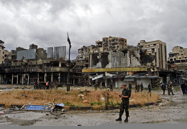 Syrian government forces inspect damages in Homs, Syria, Thursday, May 8, 2014. Carrying their rifles and small bags of belongings, hundreds of exhausted Syrian rebels withdrew Wednesday from thei ...