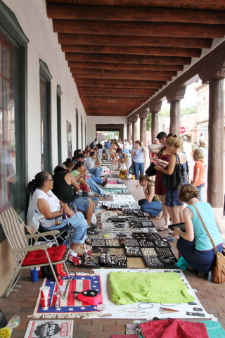 This July 14, 2010 image shows Native American artists selling their wares under the portal in front of the Palace of the Governors in the historic plaza in Santa Fe, N.M. A national historic land ...