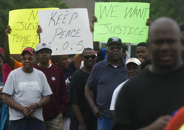Protesters carry signs while marching to the  Hearne, Texas police department Thursday, May 8, 2014 following the Tuesday shooting of 93-year-old woman.  Robertson County District Attorney Coty Si ...