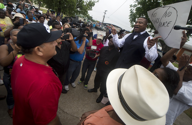 Quanell X, leader of the New Black Panther Party, right, speaks to Hearne mayor Ruben Gomez, left,  during a rally outside the Hearne, Texas police department Thursday, May 8, 2014 following the T ...