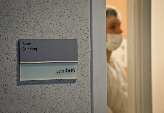 In this April 15, 2014 photo, Michael Mosco, a criminalist, prepares to enter the bone grinding room at the Office of Chief Medical Examiner in New York. The room is central to the examination of  ...