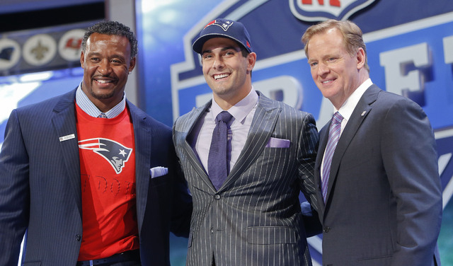 Eastern Illinois quarterback Jimmy Garoppolo poses for photos with NFL commissioner Roger Goodell and former New England Patriots linebacker Willie McGinest after being selected as the 62nd pick b ...