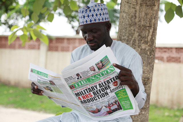 Shehu Haruna reads a local newspaper with headlines declaring that the Military were alerted before the abducution of secondary school girls in Chibok, on a street in Abuja, Nigeria, Saturday, May ...