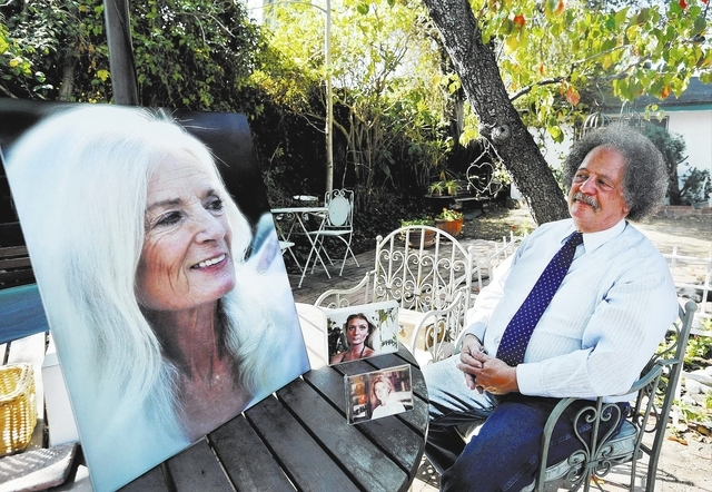 In this Wednesday, Feb. 19, 2014 photo, Jay Westbrook, clinical director of Compassionate Journey, sits next to photos of his late wife, Nancy, in their backyard in Los Angeles. There have been th ...