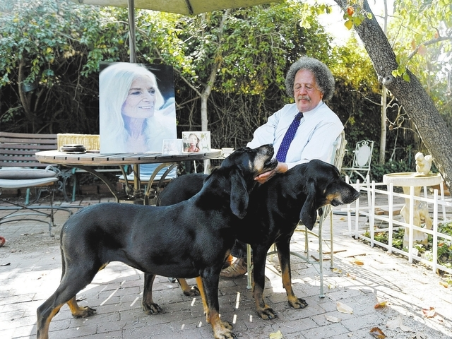 In this Wednesday, Feb. 19, 2014 photo, Jay Westbrook, clinical director of Compassionate Journey, pets his dogs as he sits next to photos of his late wife, Nancy, in their backyard in Los Angeles ...