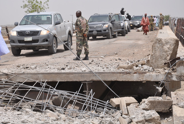 A soldier and other government officials inspect the bridge that was bombed on Sunday, May 11, 2014, after an attack by Islamic militants last week in Gambaru, Nigeria. Many brutalized residents o ...